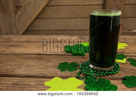 Glass of green beer, beads and shamrock for St Patricks Day on wooden table