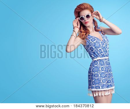 Fashion Redhead Model in Sexy Jumpsuit, woman in Trendy Summer Dress. Stylish wavy hairstyle, fashion Sunglasses, Summer Floral Outfit. Glamour fashion pose. Playful Beauty Girl, Luxury summer Lady