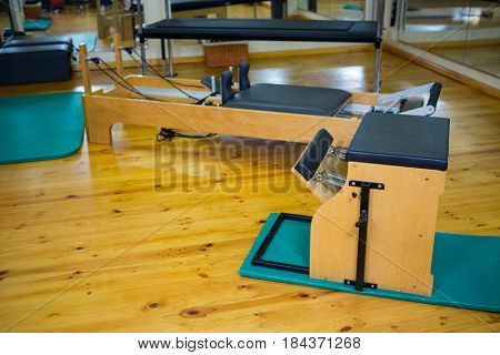 Reformer and wunda chair on wooden floor in gym