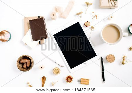 Blogger or freelancer workspace with tablet coffee mug notebook sweets and accessories on white background. Flat lay top view minimalistic brown styled home office desk. Beauty blog concept.