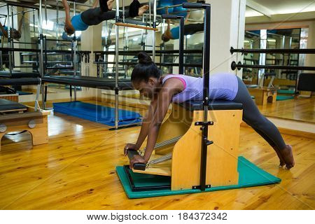Determined woman exercising on wunda chair in gym