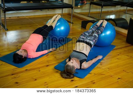 Determined women exercising with fitness ball in gym