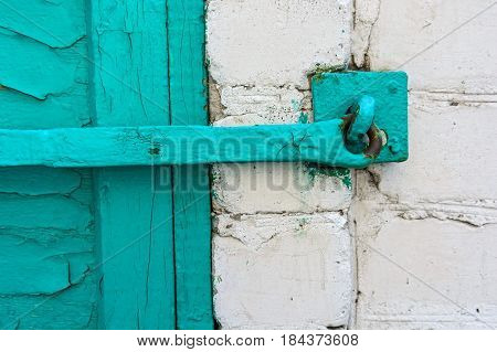 Close up obsolete cyan wooden window shutters locked with long metal hasp
