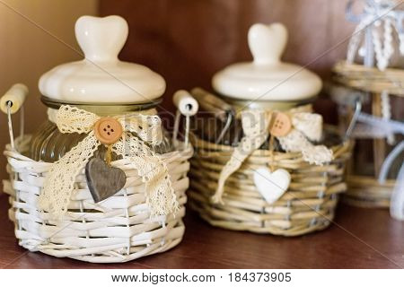 Close up white sugar cubes in white sugar bowl and sugar tongs on wooden table