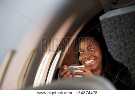 African American businesswoman drinking on private jet