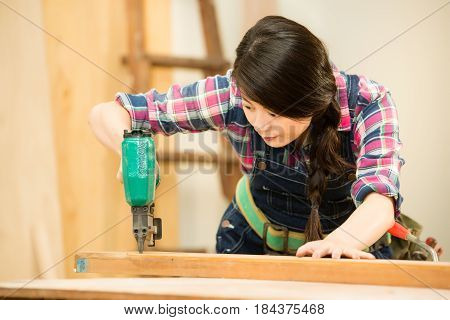 Woodworker Using Air Compressor Nail