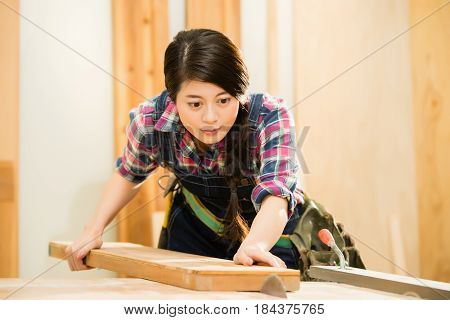 Young Female Carpenter Cutting Wood
