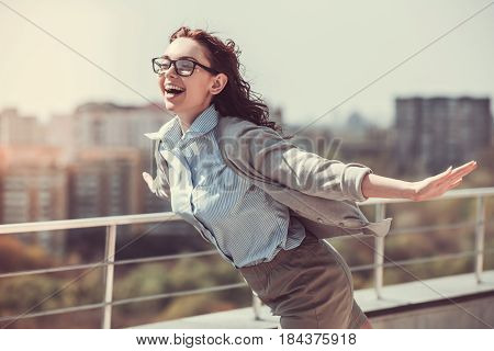 Beautiful young business woman is imitating flight and smiling while resting outdoors