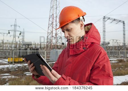 Engineer at electrical substation using a tablet computer. Electrical power industry