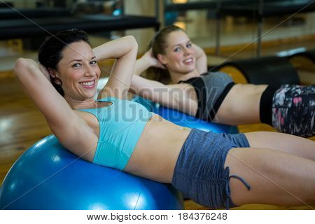 Portrait of happy women exercising on fitness ball in gym