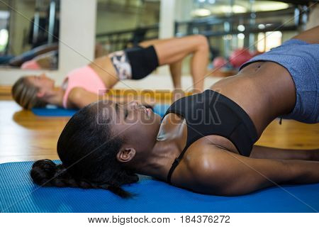 Smiling fit woman doing stretching exercise on mat in fitness studio