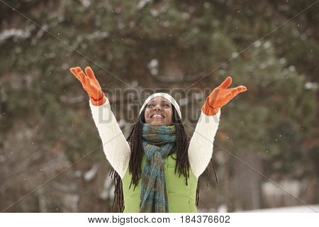 African American woman with arms outstretched in the snow