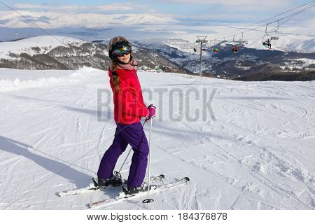 Girl in ski goggles poses on mountain with cableway in ski resort at winter day