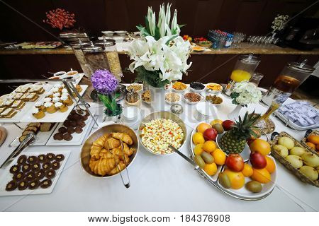 Morning buffet in hotel - many fruits, bakery products and other food are on table