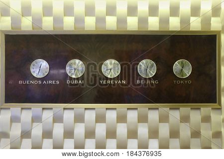 Five clocks are on stylish wall and show different timezones - it is decoration in hotel