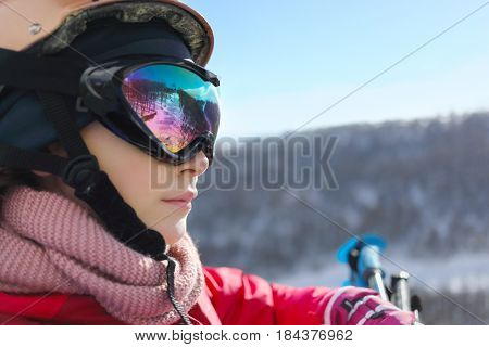 Girl in ski goggles looks away during lifting at cableway in ski resort at winter day