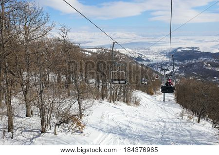 People ride in chairs of cableway among trees at winter day in Cahkadzor resort in mountains, Hrazdan town far away