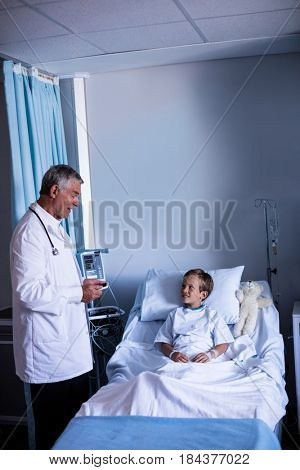 Male doctor interacting with patient during visit in ward at hospital