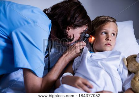 Female doctor examining patient ear with otoscope at hospital