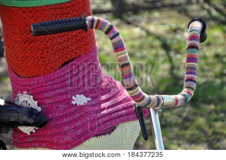 Knitted tree and bicycle striped handlebar close up.