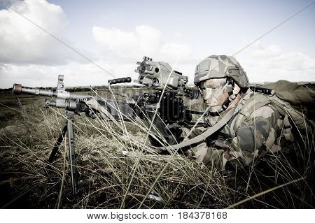Normandy France- August 4 2011. Legionnaire in combat ammunition and with a rifle with an optical sight in the open area during training firing