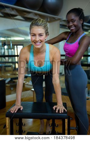 Portrait of smiling trainer assisting woman with wunda chair in fitness studio