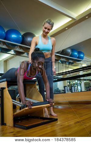 Smiling trainer assisting woman with wunda chair in fitness studio