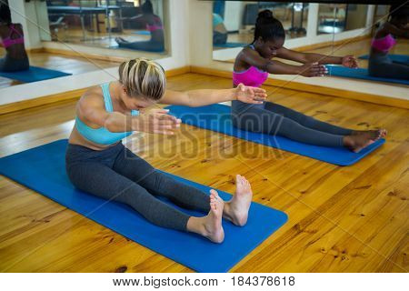 Two fit women doing stretching exercise on mat in fitness studio