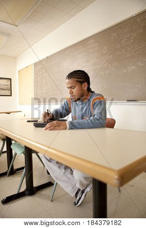 Peruvian student studying in classroom on laptop