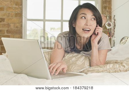 Korean woman laying on bed using laptop and talking on phone