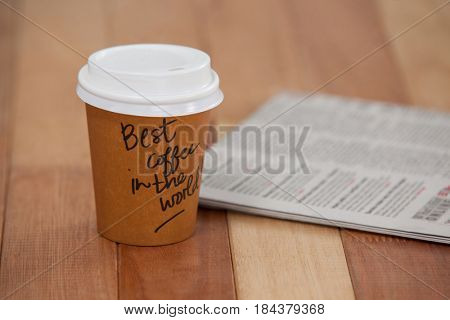 Close-up of disposable coffee cup and newspaper on wooden background