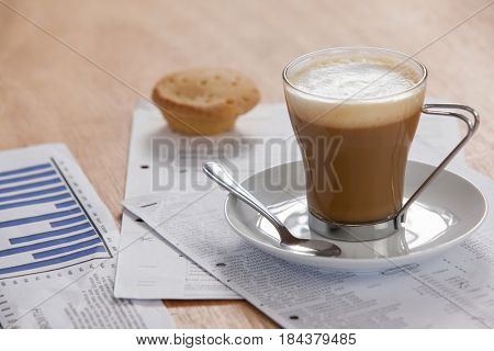 Coffee cup with saucer, spoon and documents on wooden background