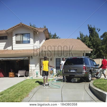 Black family washing car in driveway