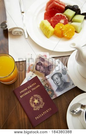 Chinese passport and money on breakfast table