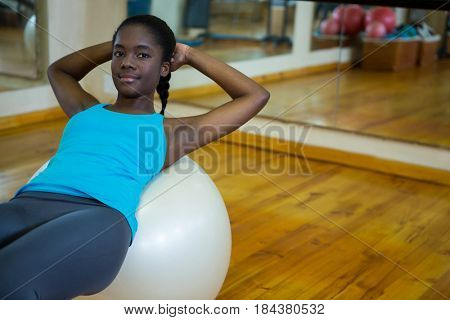 Portrait of fit woman exercising on fitness ball in fitness studio