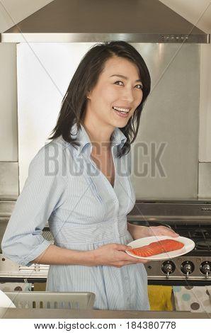 Korean woman holding salmon steak on plate