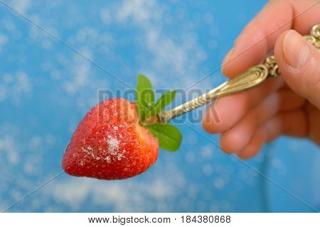 A heart shaped strawberry in spoon and sugar on background