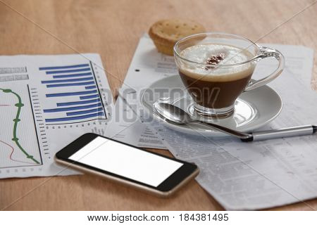 Coffee cup with document and mobile phone on wooden background
