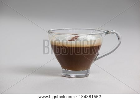 Transparent coffee cup with creamy froth on white background