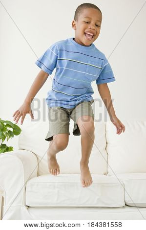 African American boy jumping off sofa