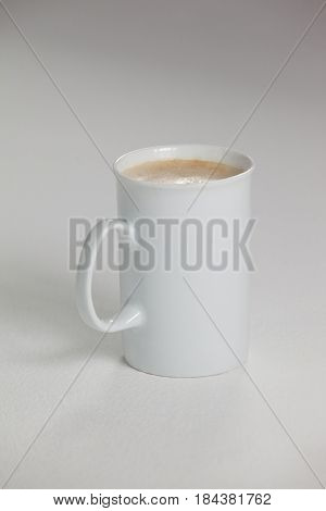 White mug of coffee with creamy froth on white background