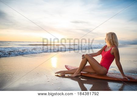 Attractive girl with a surfboard outdoors