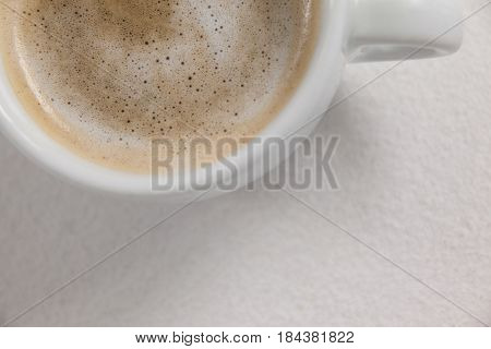 Close-up of white coffee cup with creamy froth on white background
