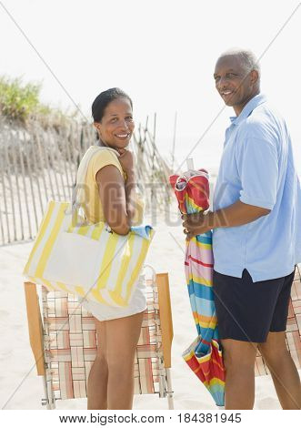 Black couple carrying beach gear together