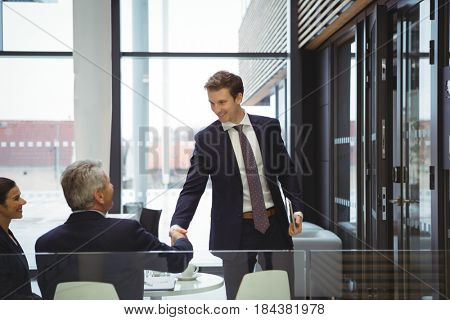 Businesspeople shaking hands in a lobby at office