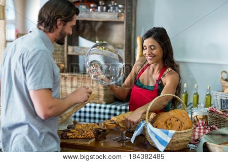 Bakery staff showing snack to the male customer at counter in bake shop