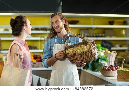 Smiling vendor holding a basket of potatoes while interacting with woman at the grocery store