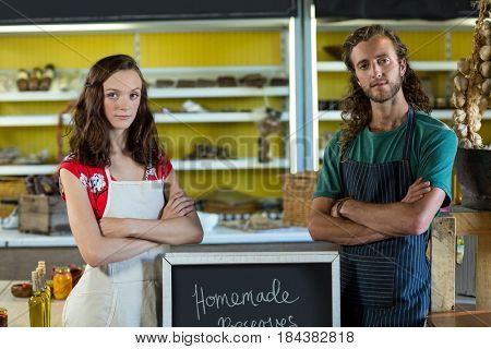 Shop assistants standing with their arms crossed at grocery shop