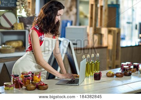 Female shop assistant using laptop at the counter in grocery shop