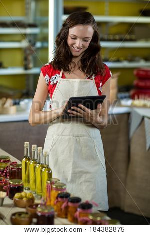 Female shop assistant using digital tablet at the counter at grocery shop